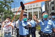 昨日多名區議員(左方)到設立氣膜實驗室的中山紀念公園體育館外抗議,期間警員多次警告違反「限聚令」,又拉起封鎖線,多名區議員被票控。(林若勤攝)