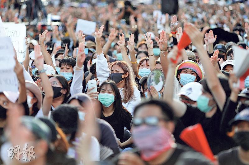 昨在曼谷出席反政府示威的民眾不少是年輕人,他們高舉3根手指,代表三大訴求和抗爭精神。(路透社)