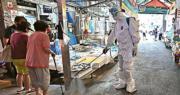 韓國衛生當局人員昨日身穿全套保護衣物,在首爾的愛心第一教會附近一個街市噴灑消毒劑。(法新社)