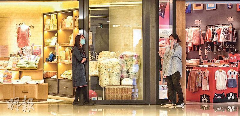 零售市道低迷,旺角一商場內人流少,兩間嬰兒服裝店的職員在閒聊。(賴俊傑攝)