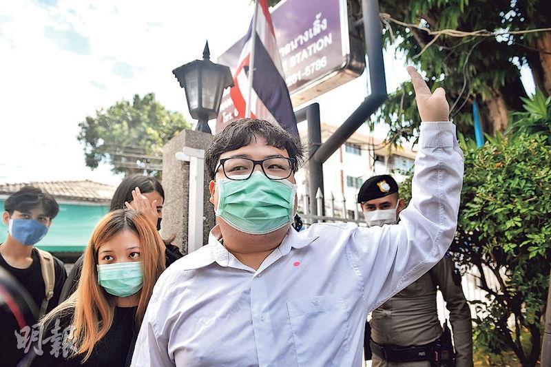 泰國示威領袖巴利(Parit Chiwarak,前)昨日到曼谷一間警署報到,其間舉起3根手指象徵抗爭手勢。(法新社)