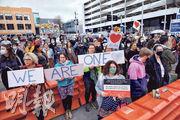 昨日是新西蘭基督城清真寺恐襲案量刑聆訊最後一天,有民眾在法庭外手舉「我們團結一致」標語牌集會,以示支持死傷者家屬。(法新社)