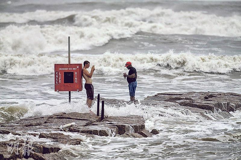 在得州加爾維斯頓,周二在颶風「勞拉」逼近時海面出現大浪,有男子在岸邊拍照。(法新社)