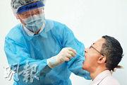香港醫務行政學院聯同多個醫護組織為參與普及社區檢測採樣的醫護及學生辦工作坊。護理專科學院副院長陳子中(左)即場示範為外科醫生林哲玄(右)採集咽喉樣本,採樣棒要深入口腔約5厘米,採樣人員不宜站在正前方,要站在對方身旁。陳示範穿裝備時保護衣破洞,無立即更換,繼續為林採樣。(馮凱鍵攝)