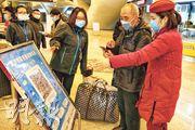 新冠疫情爆發期間,武漢官方要求必須實名註冊健康碼才能搭乘公共交通工具。圖為3月30日,義工協助不會註冊的旅客掃描二維碼完成程序。(明報記者攝)