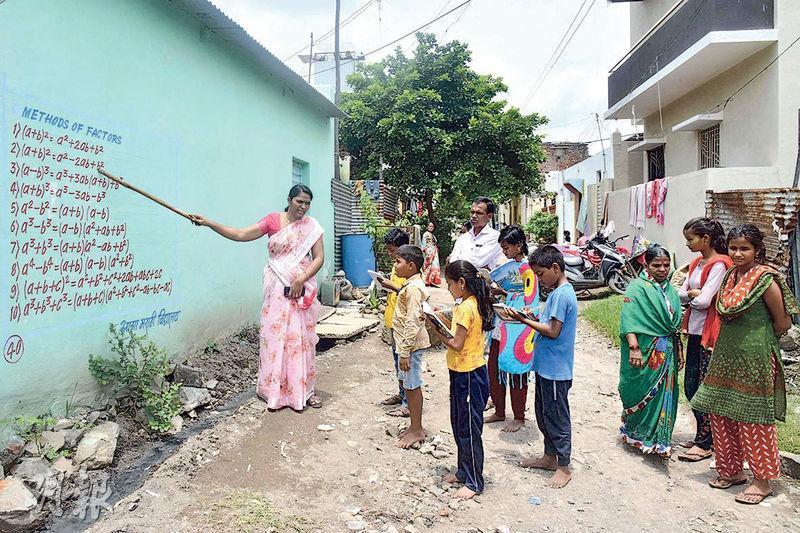 印度的新冠肺炎疫情肆虐之下,該國馬哈拉施特拉邦一名學校校長(左)上月底在房屋外牆寫滿教科書內容,教導那些因為沒有智能手機、無法透過網上學習的窮家學生。(法新社)