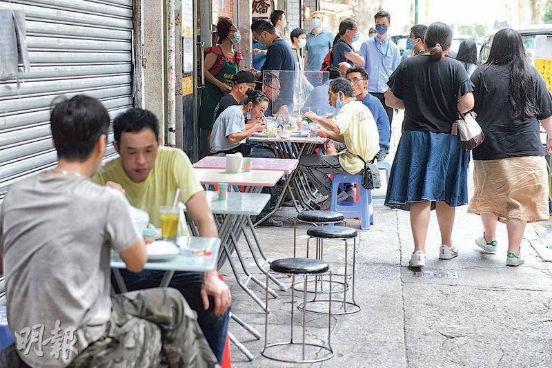 食肆每枱放寬至可坐4人,昨日午飯時間,銅鑼灣加路連山道有食肆放餐桌在室外,有3張拍在一齊的桌子以兩塊隔板隔開,5人坐在一起。(林若勤攝)