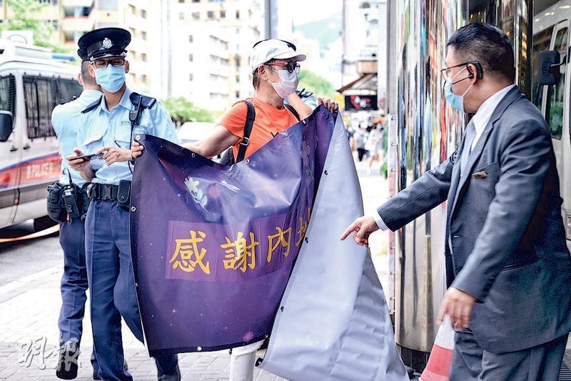 昨午有市民(橙衣者)帶同橫額到內地核酸檢測支援隊下榻的九龍維景酒店,舉行「感謝內地支援隊」集會。有拿着手機的警員在旁觀察。(賴俊傑攝)