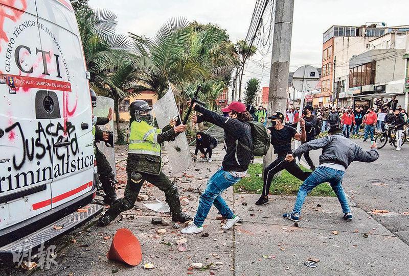哥倫比亞波哥大一名律師被拘留時遭警方暴力對待後死亡,觸發民眾示威,圖為示威者周三與防暴警察爆發衝突。(法新社)