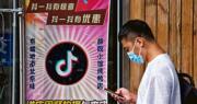 中國短影音分享程式抖音海外版TikTok美國業務的出售案變數頻生,字節跳動稱不會將TikTok賣給微軟。圖為9月14日,北京一名男子在貼有抖音標貼的餐廳走過,招牌顯示用餐時使用抖音發布短片將獲得優惠。(法新社)