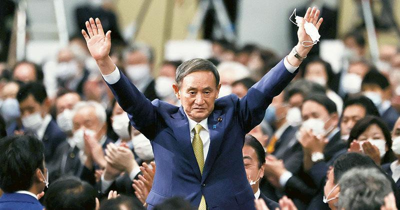 菅義偉(中)周一在東京高票當選日本自民黨總裁之後,高舉雙手向在場者致意。他周三獲國會正式通過任命後,將接替安倍晉三完成餘下約一年的首相任期。(路透社)