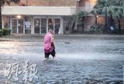 阿拉巴馬州周二在颶風「薩利」吹襲下風雨交加,當地格爾夫海岸一名男子走過水深及膝的停車場。(法新社)