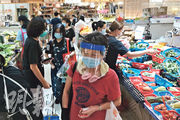 頌富街市一名感染源頭不明的60歲菲傭昨日確診,她曾光顧天水圍頌富街市,衛生防護中心將會到街市派發樣本瓶。昨日所見,該街市人頭湧湧,有人買餸時戴上透明面罩。(馮凱鍵攝)