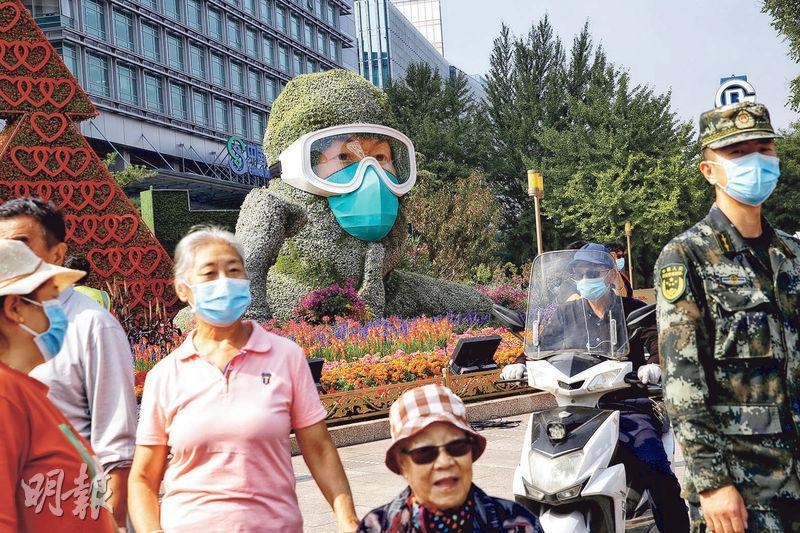 青島再有本地感染個案,可能影響十一長假民眾的出行安排。圖為北京街頭的節慶花壇,也佈置成戴口罩的醫護人員。(路透社)