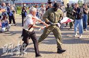 白俄羅斯73歲示威名人「尼娜婆婆」巴金斯卡婭(左)前日不甘防暴警察搶奪她的舊版國旗,追逐理論而被捕。(法新社)