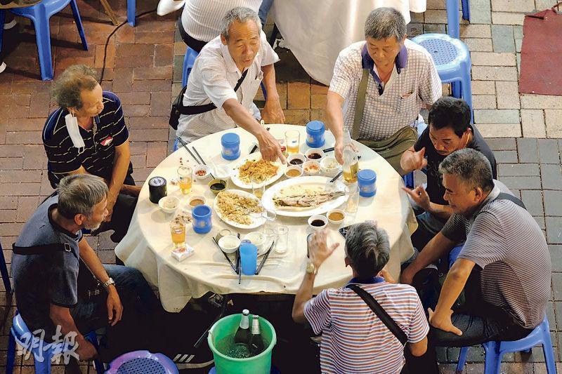 昨晚在元朗的一家大排檔,有食客7人一枱猜枚暢飲,違反政府規定食肆每枱限坐4人。政府今起修例,若食客違規,除了食肆負責人會犯法,食客亦會因違反限聚令而被票控。(鄧宗弘攝)