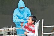 印度南部城市海得拉巴市一名衛生部門人員,周一為一名男孩做鼻咽拭子核酸測試,檢測有否感染新型冠狀病毒。該國的新型冠狀病毒患者已超過600萬人。(法新社)