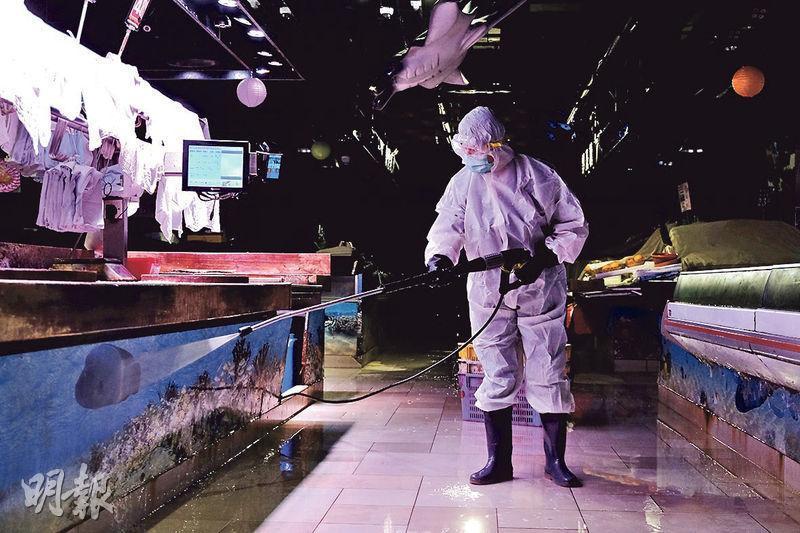 昨公布的一宗源頭不明個案,為居於青衣長宏邨的27歲泰裔主婦,她常到青衣長發街市及青衣城。昨有穿著全副裝備的人員(圖)到長發街市清潔消毒。(鄧宗弘攝)