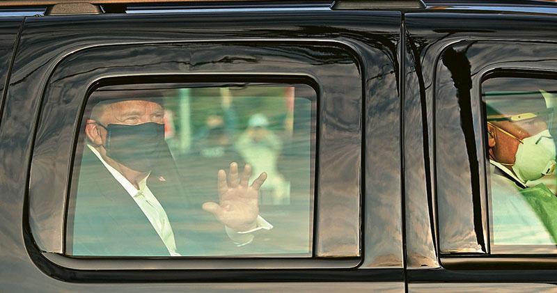 戴上黑色口罩的美國總統特朗普(左)周日短暫「出院」,在車內向聚集於他入住的醫院外聚集的支持者揮手。從相片可見,坐在車內前座的一名人員戴有貌似N95的口罩及穿著保護衣。(法新社)