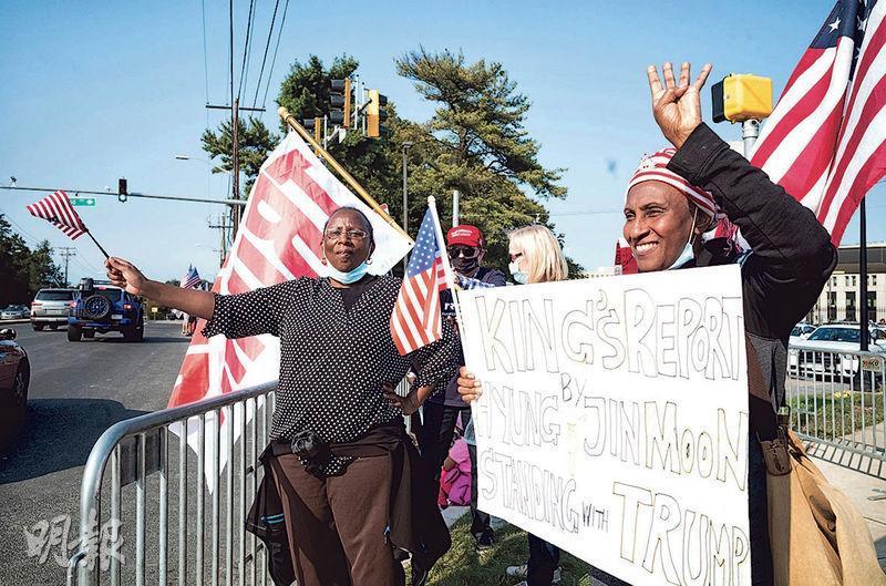 特朗普入住的華特里德國家軍事醫學中心外,周日有黑人到場揮動國旗表達支持。(路透社)