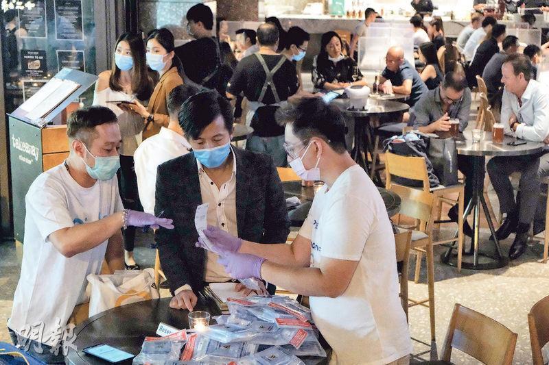 檢測承辦商Prenetics的工作人員昨晚到蘭桂坊一間酒吧內派發樣本包。(馮凱鍵攝)