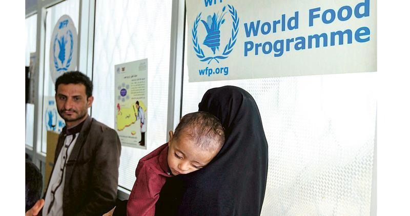 一名婦女帶同孩子到世界糧食計劃署位於也門的醫院接受治療。(法新社)
