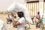 也門男子頂着一袋世界糧食計劃署的物資。(法新社)