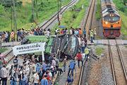 泰國差春騷府旅遊巴士(綠色)周日被火車撞倒翻側,車廂扭曲,車頂裂開。(法新社)