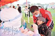 昨日青島有6名無症狀感染者確診,當局為800多萬市民驗核酸,截至目前無新個案。圖為醫護為小童採樣。(法新社)