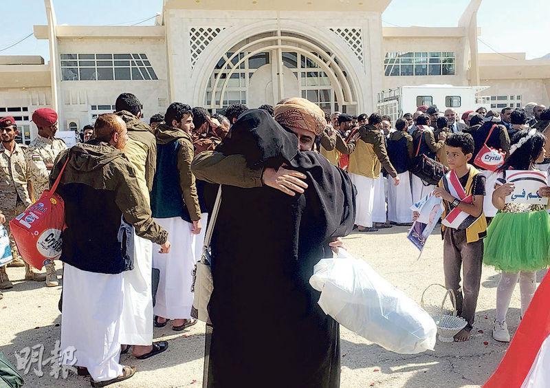 在交換人質中獲釋的沙特盟軍人員周四在也門的塞尤恩機場與親人擁抱。(路透社)