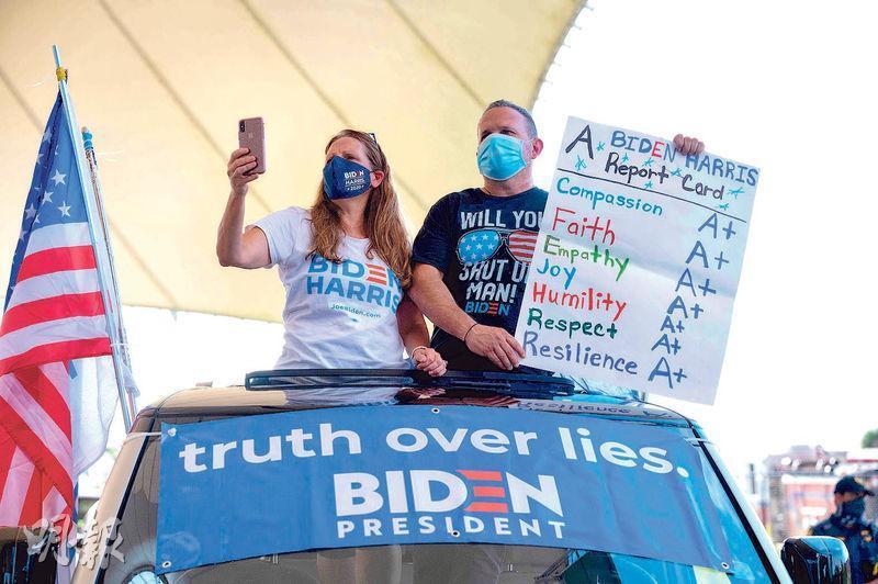 在佛羅里達的米拉馬爾,周二有拜登的支持者手持自製的「人格成績表」,指拜登及其副手賀錦麗在很多方面都是「A+」。(法新社)