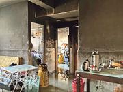 警方及化驗所人員昨早重返單位調查及蒐證。涉事單位牆身熏黑,幸石油氣罐未被波及。(黃詩雅攝)