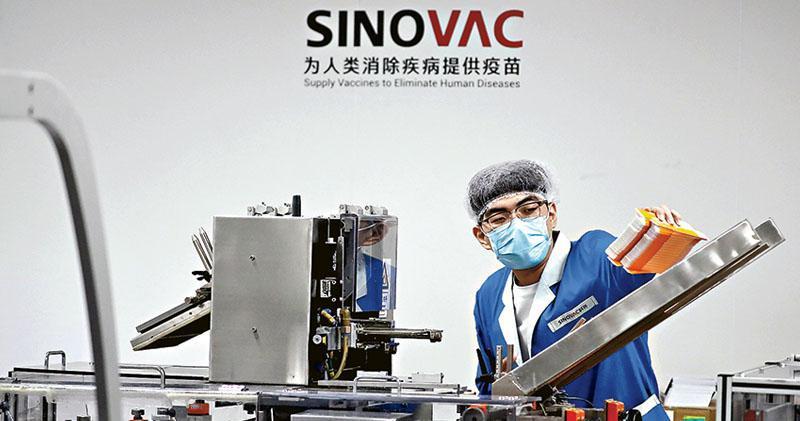 中國新冠疫苗研發處全球領先地位,巴西近日宣布將使用北京科興生物(Sinovac Biotech)研發的疫苗作為國家免疫計劃一部分。圖為9月24日,一名男子在科興生物的包裝工廠中製作疫苗。(路透社)