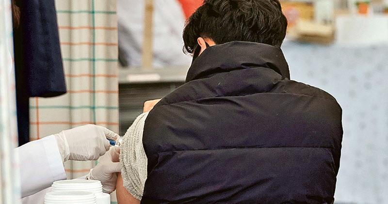 圖為韓國一名男子昨日在首爾一家醫院接種流感疫苗。(路透社)
