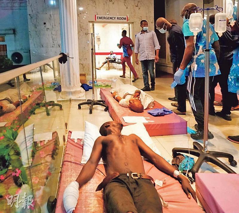 尼日利亞拉各斯(Lagos)有民眾發起反警暴示威,據傳有士兵向示威者開火造成傷亡,但州長桑沃-奧盧否認有人當場死亡。圖為他(右二)周三到醫院探望傷者。(路透社)