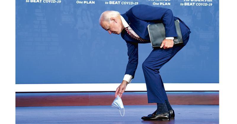 美國民主黨總統候選人拜登上周五(23日)結束競選演說時個人口罩忽然掉落,馬上彎身撿起。(法新社)
