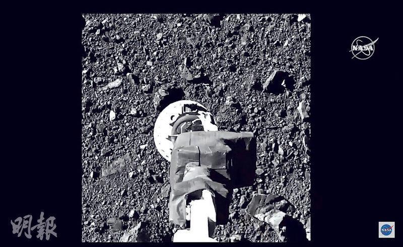 美國太空總署公布周三(21日)取得的小行星探測器Osiris-Rex以機械臂採集小行星樣本片段。(法新社)