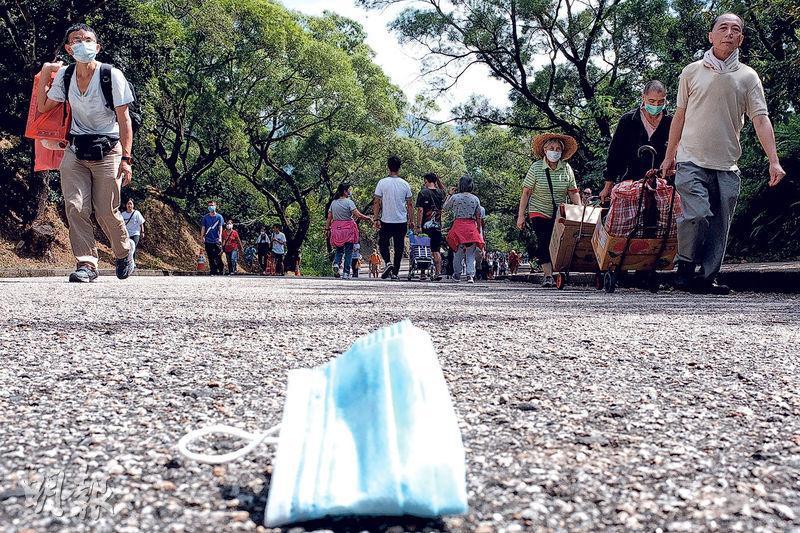 昨日為重陽節,大批市民到粉嶺和合石墳場掃墓,有人遺留口罩在地上,亦有市民沒佩戴口罩。(曾憲宗攝)