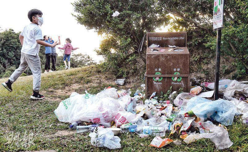 不少市民趁重陽節假期到郊外,但未有帶走垃圾。圖為大帽山上有垃圾桶滿瀉,有小童把垃圾擲向垃圾箱方向。(朱安妮攝)