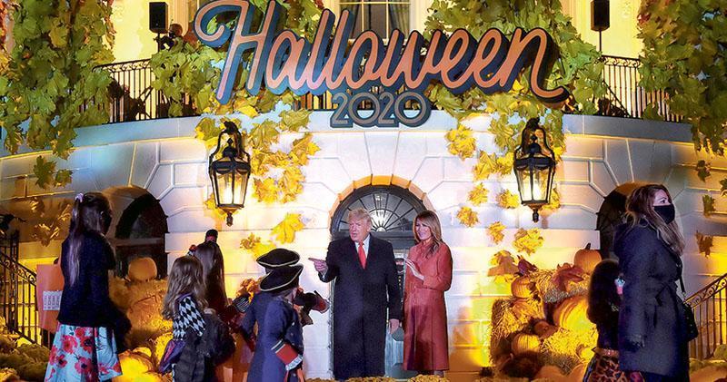 美國總統特朗普(右四)及妻子梅拉尼婭(右三)周日在白宮出席萬聖節活動,向參與活動的兒童打招呼。特朗普夫婦二人在10月初皆曾確診新冠病毒,其後康復。(法新社)