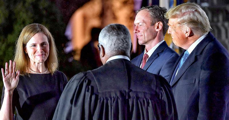 巴雷特(左)在美國總統特朗普(右一)、其丈夫(右二)見證下,周一晚在白宮南草坪向最高法院大法官托馬斯(背向),宣誓出任最高法院大法官。(法新社)