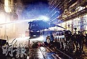 意大利警方周一出動水炮車,驅散在都靈市內抗議政府實施新一輪嚴格控疫措施的示威者。(法新社)