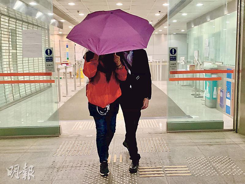 有聽障問題的被告羅鎮傑(右)否認襲警罪名,離開時以雨傘掩面離開。(戴晴曦攝)