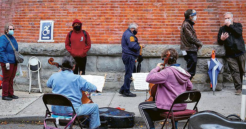 美國大選進入最後直路,多地都出現提前投票的人龍。其中屬於紐約州的紐約市布魯克林區,兩名大提琴手周二在一個票站外,為已等候數小時的選民奏樂解悶。(路透社)