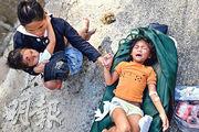 越南廣南省一名4歲女童昨日被從山泥傾瀉現場救出來,受傷的她痛極而哭,母親拉着其手安慰。(法新社)