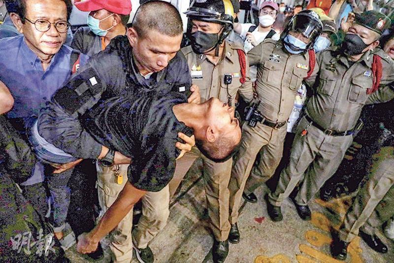 泰國反政府示威的24歲學生領袖帕努蓬(手抱者)前日獲准保釋不久即再被捕,他坐警車抵達警署其間失去知覺,其後送院。(法新社)