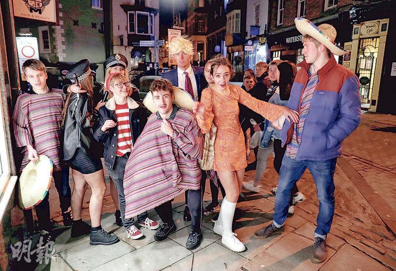 英國首相約翰遜上周六宣布新一輪全國封城措施,當晚街頭仍有不少喬裝打扮慶祝萬聖夜的民眾。(路透社)