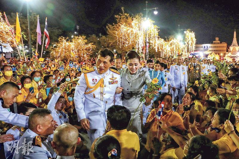 泰王哇集拉隆功(中,白衣)和王后素提達周日晚跟曼谷大王宮外擁護君主的民眾見面。(法新社)