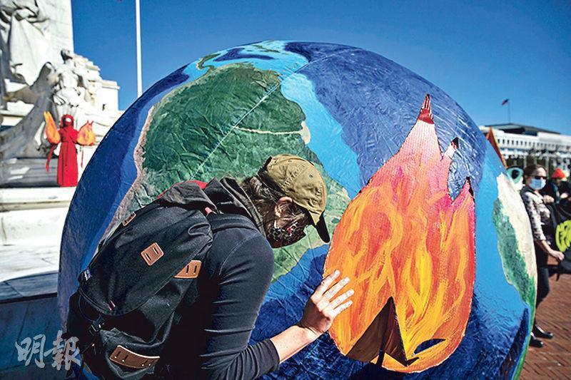 美國總統大選陷入僵局之際,美國周三正式退出對抗氣候變化的《巴黎協定》。圖為華盛頓特區周三有示威者為氣球充氣,展示一個燃燒的地球。(法新社)