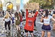 紐約市有女士上周六得悉拜登成為美國總統當選人,開心得跳入水池慶祝。(法新社)